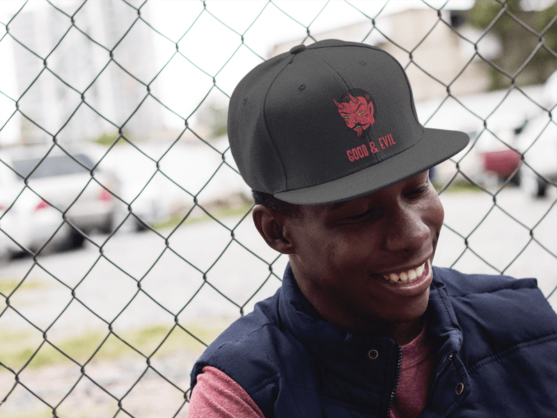 Hat Mockup Of A Smiling Black Man Leaning On A Fence