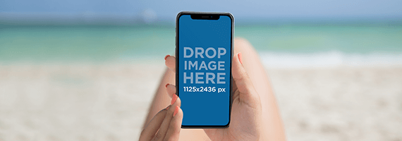 Girl Holding An Iphone X Mockup While At The Beach
