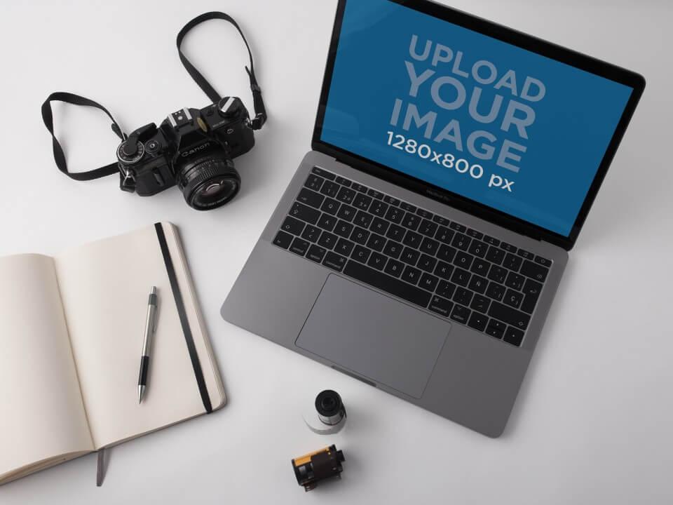 Macbook Pro Mockup Lying On A White Desk Near An Analog Camera