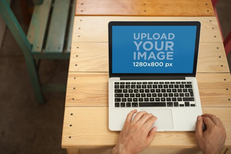 Mockup Of A Man Using A Macbook On A Wooden Table