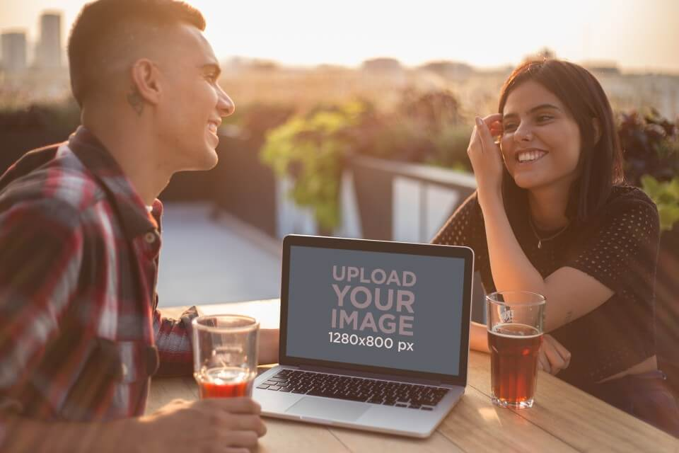 Man And Woman Laughing With A Macbook Mockup On The Table