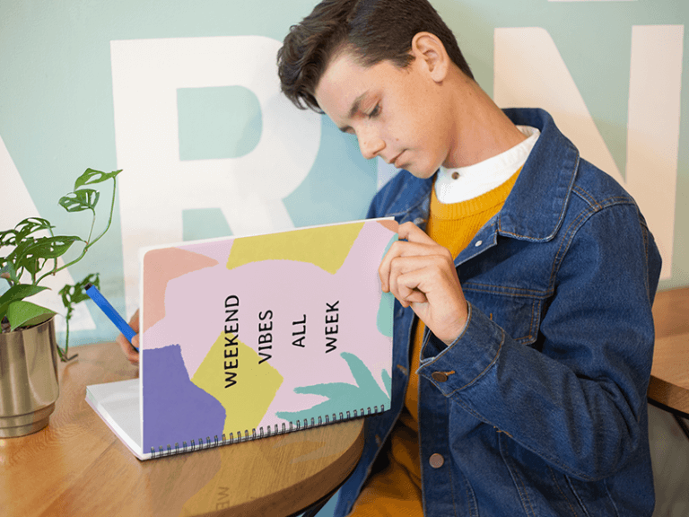 Mockup Of A Boy Reading From His Notebook In A Cafe