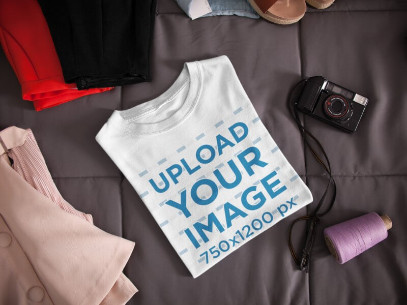 Folded T Shirt Mockup Lying Next To A Camera And Clothes On A Bed A16941
